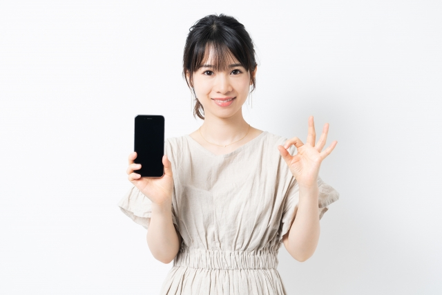 iphone12miniを手に持ってOKサインを出す女性
